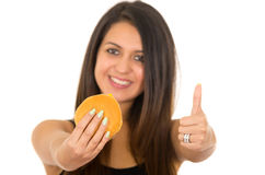 Beautiful young woman posing eating hamburger while giving thumb up to camera, smiling happily, white studio background.  Royalty Free Stock Photo