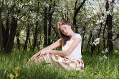 Beautiful young woman posing in a flowering garden sitting on the grass. Spring portrait in nature Royalty Free Stock Photos