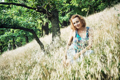 Beautiful young woman posing in the grass on the slope of hill Royalty Free Stock Image