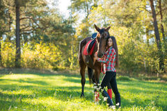 Beautiful young woman posing with a horse outdoor Royalty Free Stock Photo