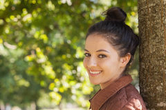 Beautiful young woman posing leaning against a tree Stock Photo