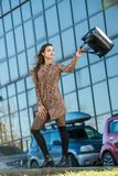 Beautiful young woman posing with a leather bag in a dress Royalty Free Stock Photos