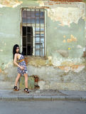 Beautiful young woman posing next to an old wall. Pretty young woman posing next to old windows and old wall royalty free stock photo