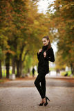 Beautiful young woman posing outdoors. Beautiful young woman with black coat and trousers posing outdoors royalty free stock images
