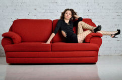 Beautiful and young woman posing on a red couch. Stock Images