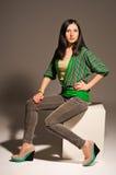 Beautiful young woman posing sitting. Beautiful young woman posing while sitting on a cube Royalty Free Stock Images