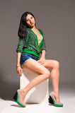 Beautiful young woman posing sitting. Neutral background Royalty Free Stock Photography
