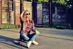 Beautiful young woman posing with a skateboard, fashion lifestyl Stock Photos