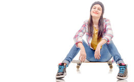 Beautiful young woman posing with a skateboard, seat on skate Stock Image