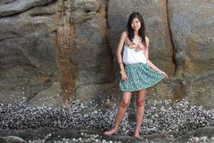 Beautiful young woman posing on stones near sea Stock Image