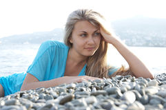 Beautiful young woman posing on stones near sea Stock Photo