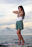 Beautiful young woman posing on stones near sea Royalty Free Stock Photography