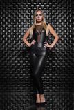 Beautiful young woman posing in the studio. Dressed in a black leather suit royalty free stock photos