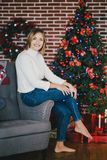 Beautiful young woman posing under Christmas tree Stock Photo