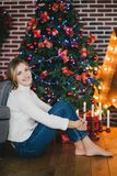 Beautiful young woman posing under Christmas tree Royalty Free Stock Images