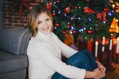Beautiful young woman posing under Christmas tree royalty free stock photos
