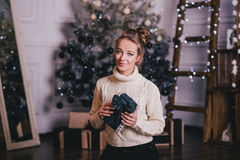 Beautiful young woman posing under Christmas tree in a holiday interior Royalty Free Stock Images