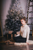 Beautiful young woman posing under Christmas tree in a holiday interior Stock Photo