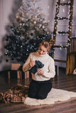 Beautiful young woman posing under Christmas tree in a holiday interior Royalty Free Stock Photos