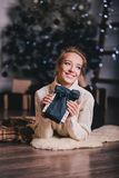 Beautiful young woman posing under Christmas tree in a holiday interior Stock Images