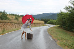 A beautiful young woman is posing on a wet road. A scene with a beautiful young woman who is posing with a red umbrella and an old - fashioned suitcase on a wet Royalty Free Stock Photo