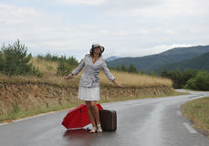 A beautiful young woman is posing on a wet road. A scene with a beautiful young woman who is posing with a red umbrella and an old - fashioned suitcase on a wet Stock Photos
