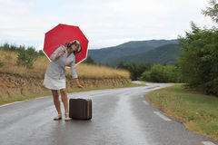 A beautiful young woman is posing on a wet road. A scene with a beautiful young woman who is posing with a red umbrella and an old - fashioned suitcase on a wet Stock Photography