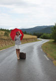 A beautiful young woman is posing on a wet road. A scene with a beautiful young woman who is posing with a red umbrella and an old - fashioned suitcase on a wet Royalty Free Stock Photography
