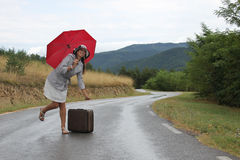 A beautiful young woman is posing on a wet road. A scene with a beautiful young woman who is posing with a red umbrella and an old - fashioned suitcase on a wet Royalty Free Stock Image