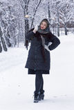 Beautiful young woman posing in winter park, plus size model on a snowy background. Full length portrait Stock Photos