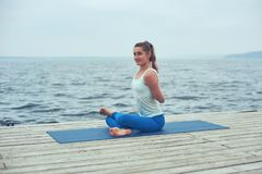 Beautiful young woman practices yoga asana Gomukhasana - Cow face pose on the wooden deck near the lake stock photos