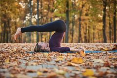 Beautiful young woman practices yoga asana Halasana Plough pose on the wooden deck in the autumn park. Beautiful young woman practices yoga asana Halasana stock photography