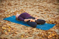 Beautiful young woman practices yoga asana Matsyasana - Fish pose on the wooden deck in the autumn park. Stock Photography