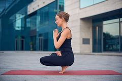 Beautiful young woman practices yoga asana Padangustha Padma Utkatasana - Half Lotus Toe Balance pose outdoors against the backgro. Und of a modern city stock image