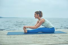Beautiful young woman practices yoga asana Paschimottanasana - forward bend pose on the wooden deck near the lake royalty free stock photo