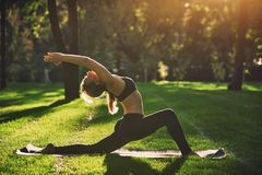 Beautiful young woman practices yoga asana Virabhadrasana 1 - warrior pose 1 in the park at sunset Stock Image