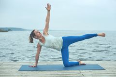 Beautiful young woman practices yoga asana on the wooden deck near the lake royalty free stock photography
