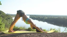 Beautiful young woman practices yoga moves and positions outdoors on an incredible clifftop. Stock Photo