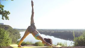 Beautiful young woman practices yoga moves and positions outdoors on an incredible clifftop. Royalty Free Stock Photo