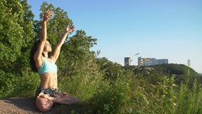 Beautiful young woman practices yoga moves and positions outdoors on an incredible clifftop. Stock Image