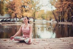 Beautiful young woman practices yoga asana on the wooden desk in the autumn park. stock photography
