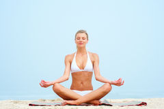 Beautiful young woman practicing yoga at the beach Royalty Free Stock Image