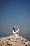 Beautiful young woman practicing yoga on the beach Stock Photo