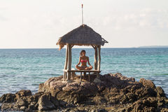 Beautiful young woman practicing yoga at the beach at sunset. Concept of healthy lifestyle Royalty Free Stock Photos