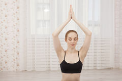 Beautiful young woman practicing yoga at home on mat - meditation Stock Images