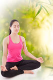 Beautiful young woman practicing yoga, sitting in a lotus positi Stock Image