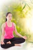 Beautiful young woman practicing yoga, sitting in a lotus positi Stock Image