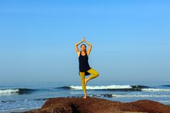 Beautiful young woman practicing yoga and stretching exercises at the summer ocean beach royalty free stock photos