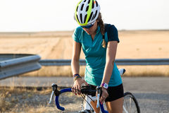 Beautiful young woman preparing for cycling on road. Stock Photos
