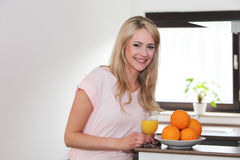 Beautiful young woman preparing fresh orange juice Stock Images